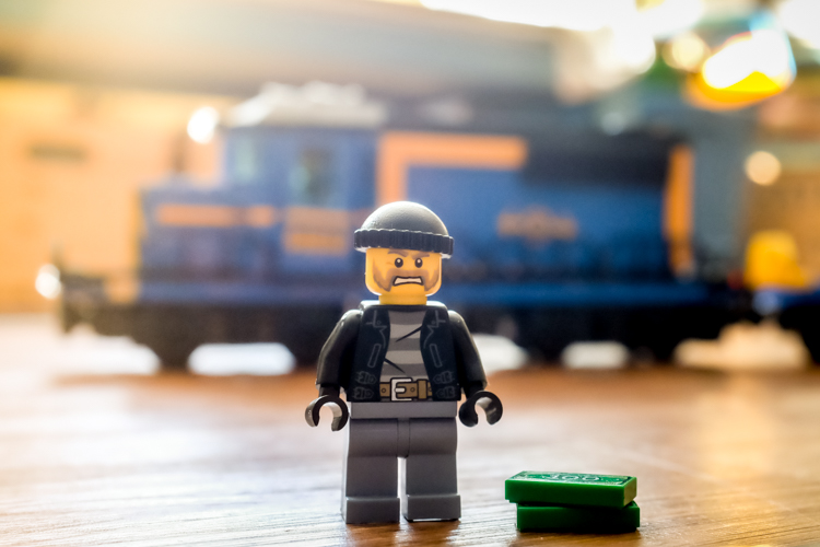 Lego man with a Lego train behind him.