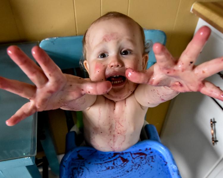 一个小孩的图片有设法杂乱的手指的接触照相机。家庭生活