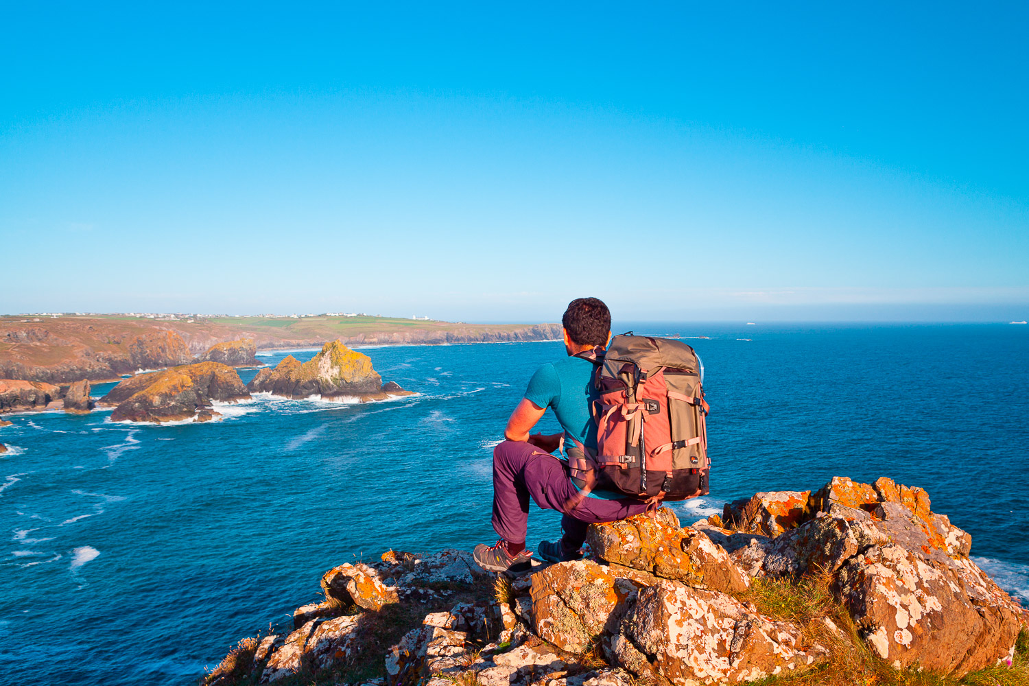 5 Camera Bags That Every Travel Photographer Needs - man sitting on a rock by the ocean