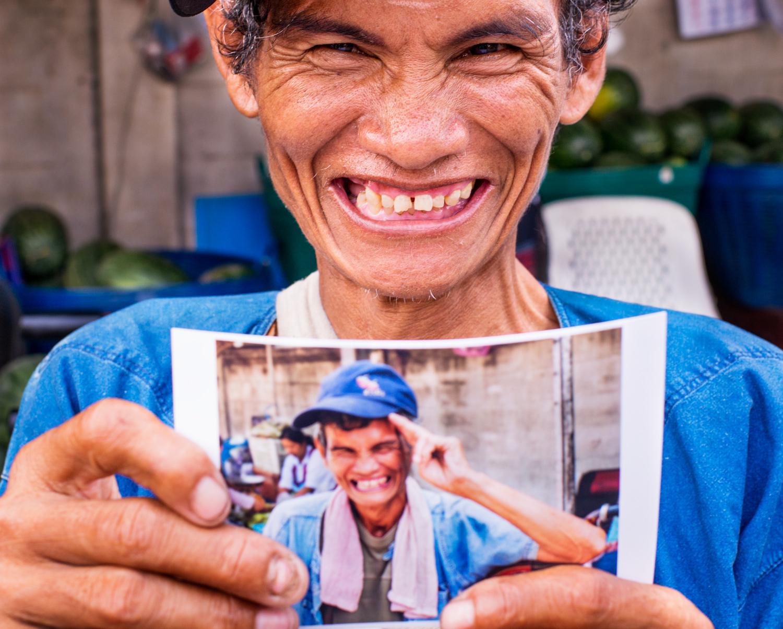 男子手持自己的照片 - 帮助您克服拍摄人物恐惧的4个技巧
