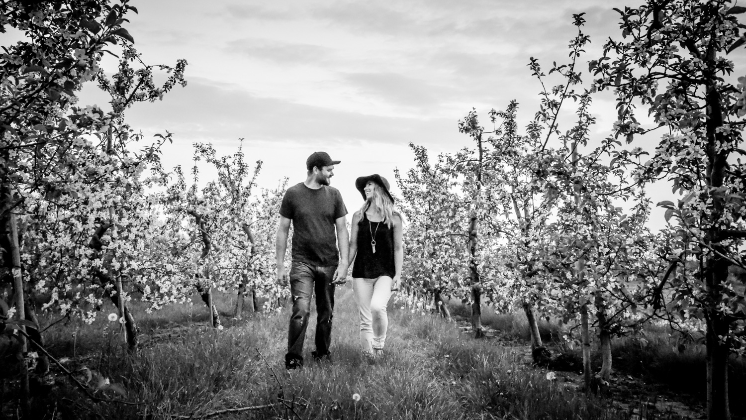 Couples photo walking between blossoming trees - Fun Ways to Photograph Couples That are a Bit Awkward
