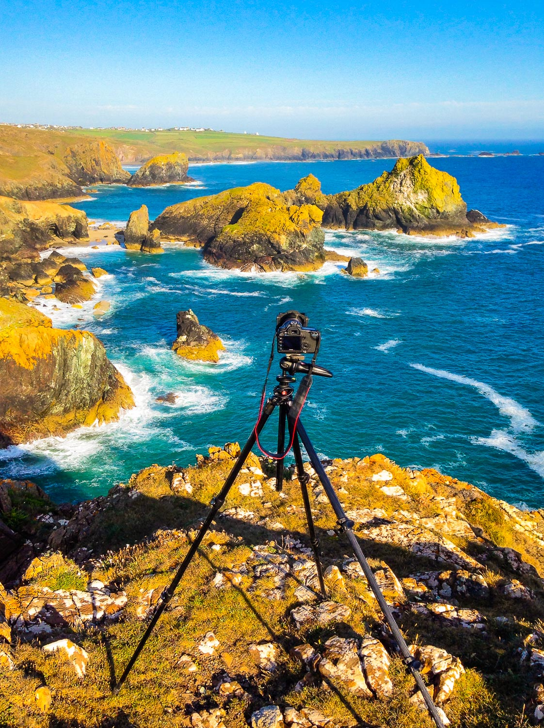 camera on a tripod overlooking a landscape scene - The First 10 Things You Need to Buy After Your Camera for Travel Photography