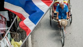 Market scene with Thai flag and samlor. Photo by Kevin Landwer-Johan (copyright)