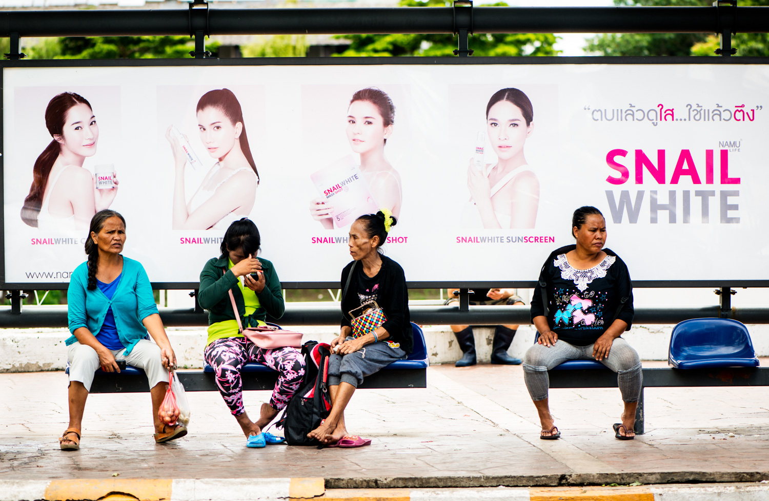 women in a bus stop in Thailand. Photo by Kevin Landwer-Johan (copyright)