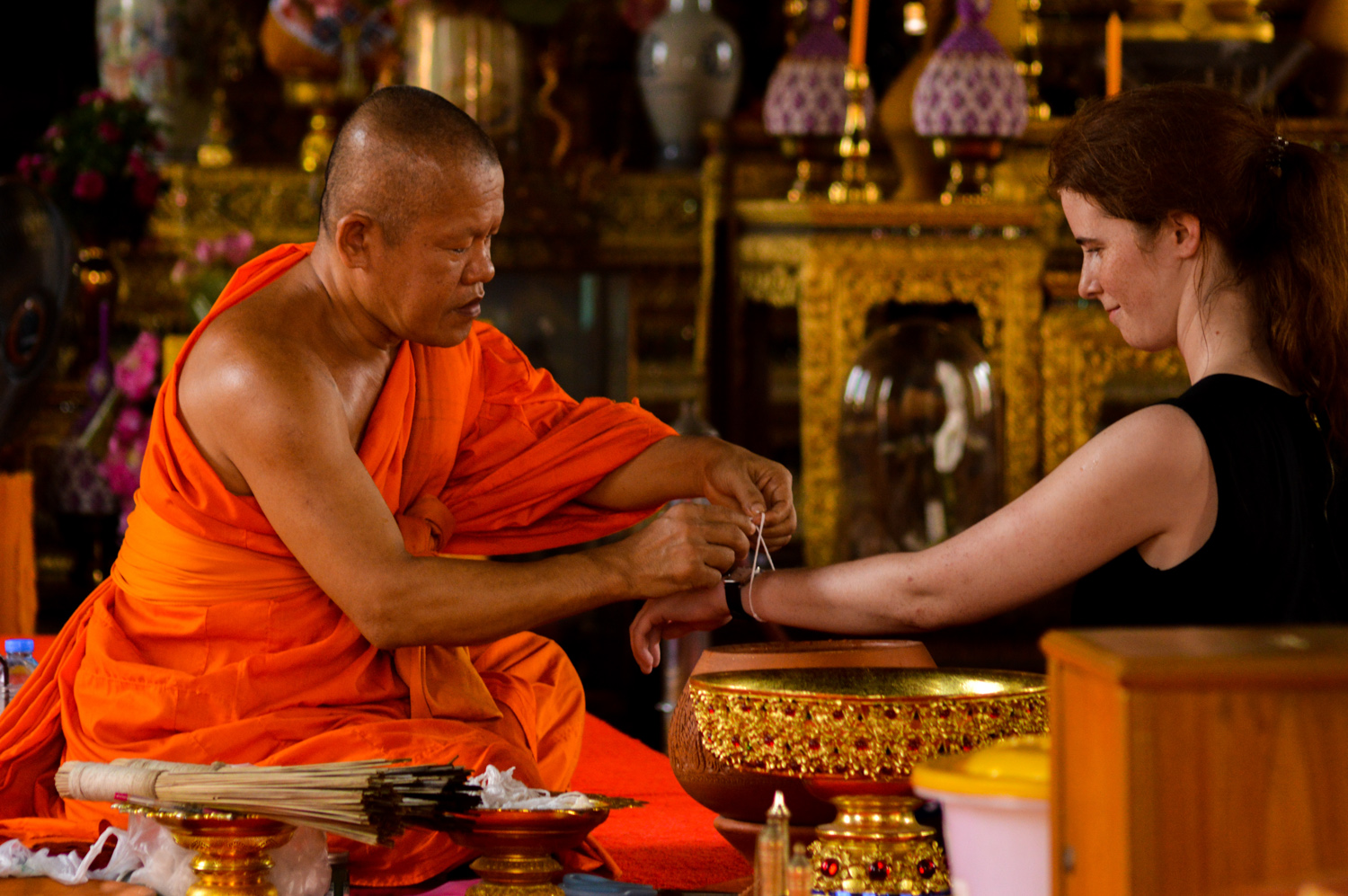 lady buying a bracelet from a monk - Six Non-Photography Tips to Super-Charge Your Travel Photography