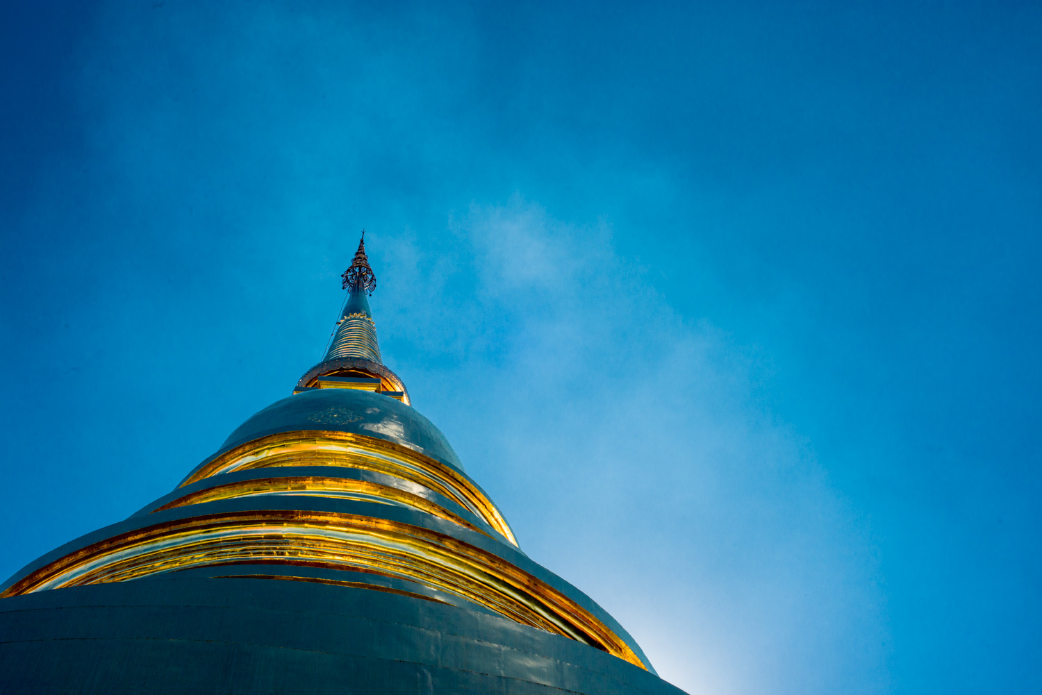 gold Buddhist chedi against a blue sky taken during a Chiang Mai Photo Workshop ©Kevin Landwer-Johan