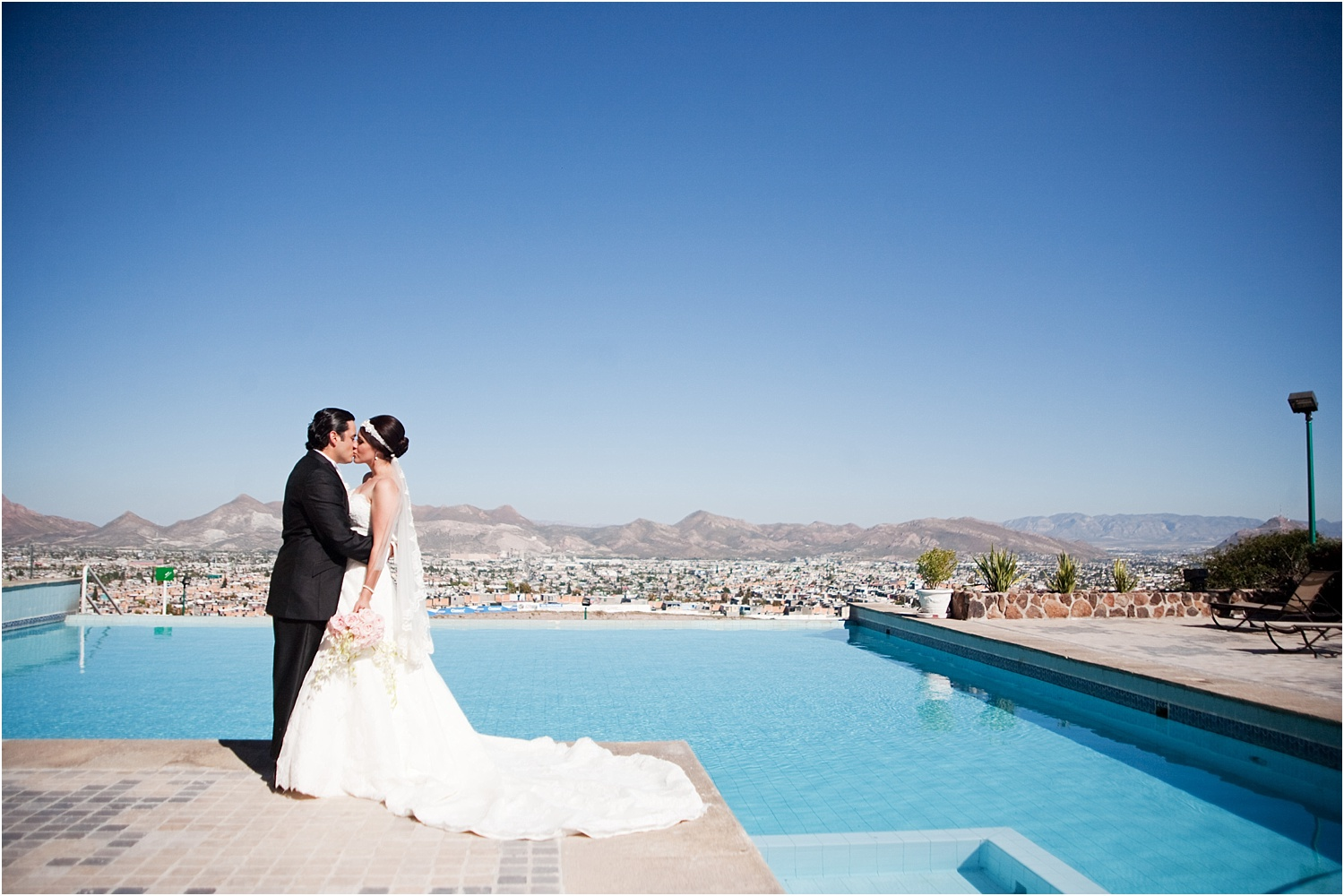 the bride and groom are kissing by the pool - How to make the portrait photograph in the midday sun