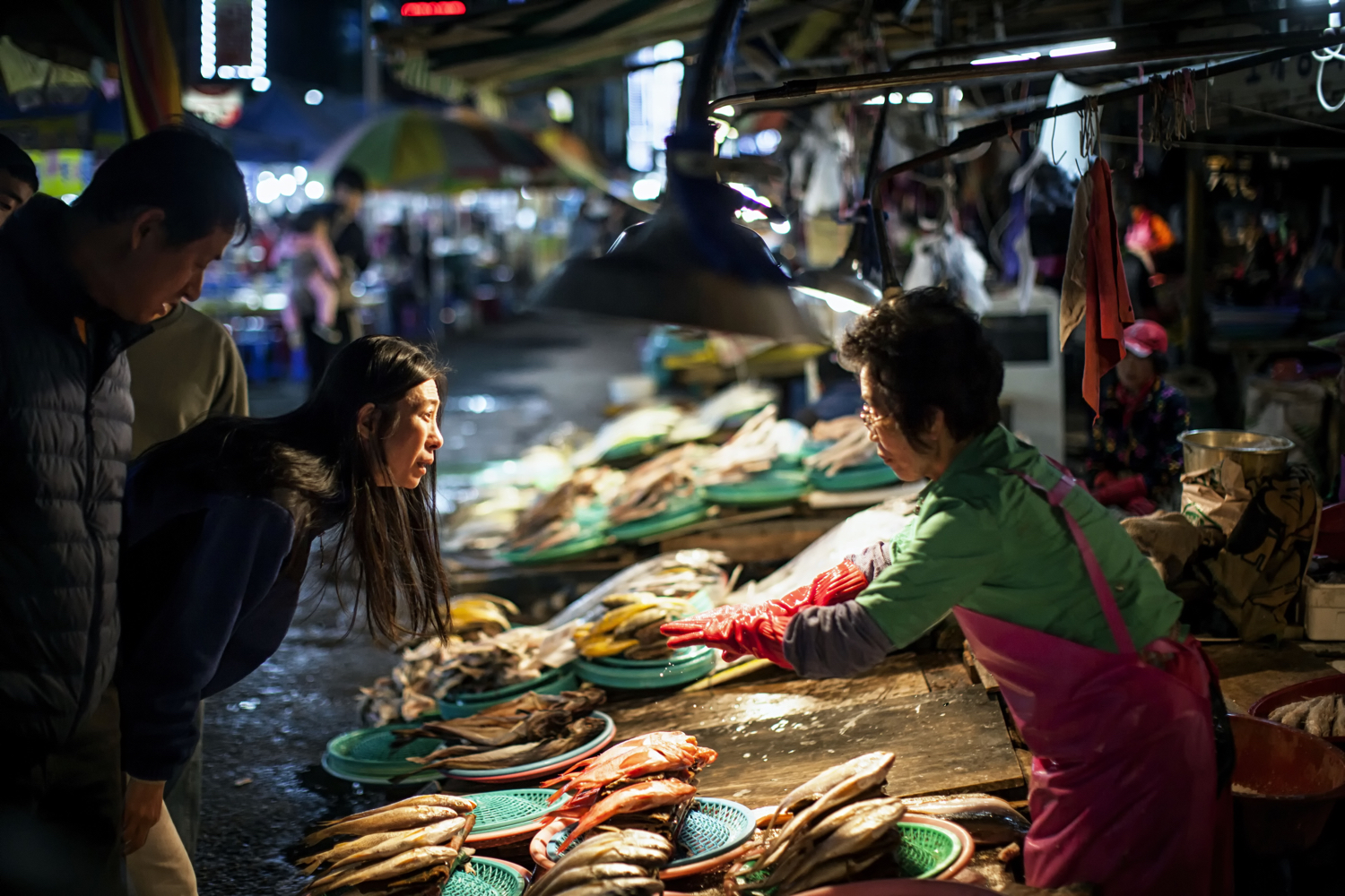 Image: In this photo, a longer focal length of 135mm was used. Markets are great for interactions be...