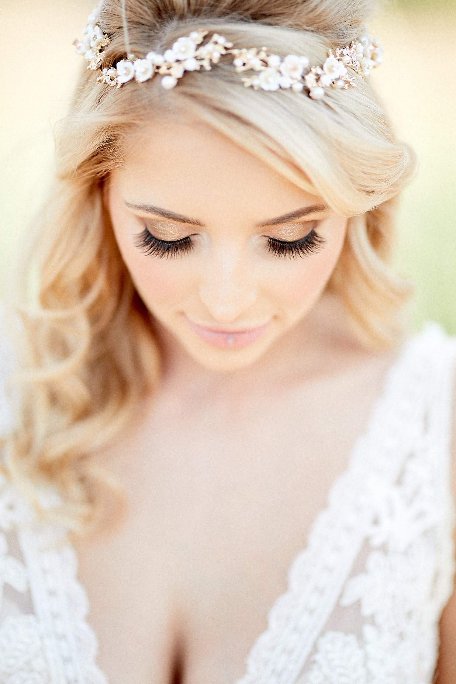 A model in a bridal dress looks down, showing her makeup.