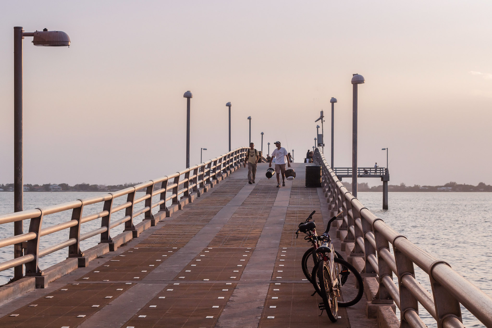 Fishermen walking down a long fishing pier.