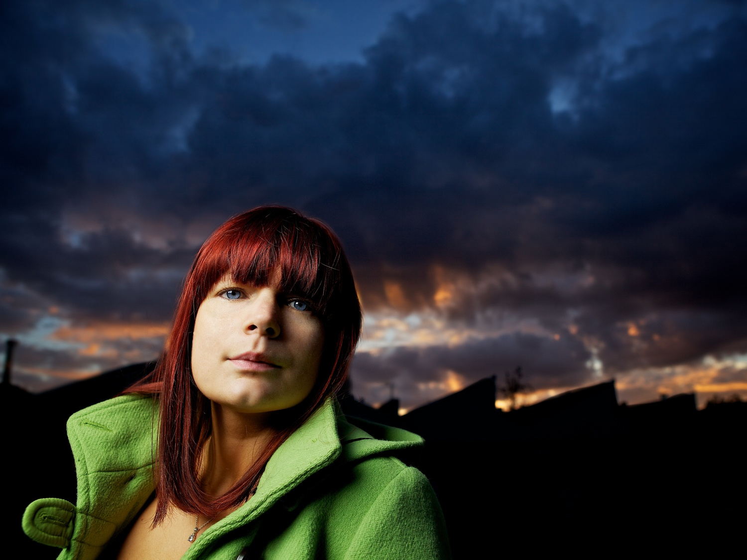 Off-camera flash in photography with a simple umbrella of a woman in a green coat at sunset