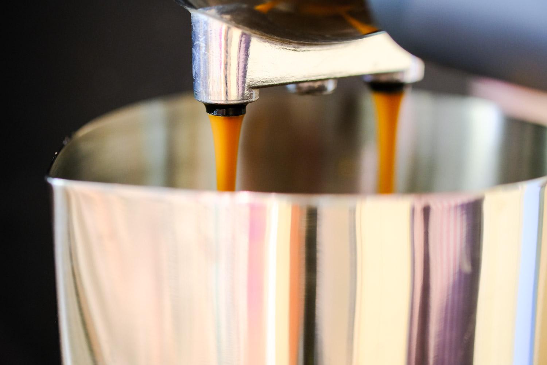 Espresso pouring into a metal jug