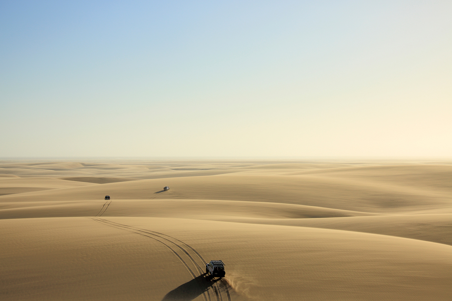 Bruce Dorn photography, shows cars driving across a sandy desert from a high perspective.