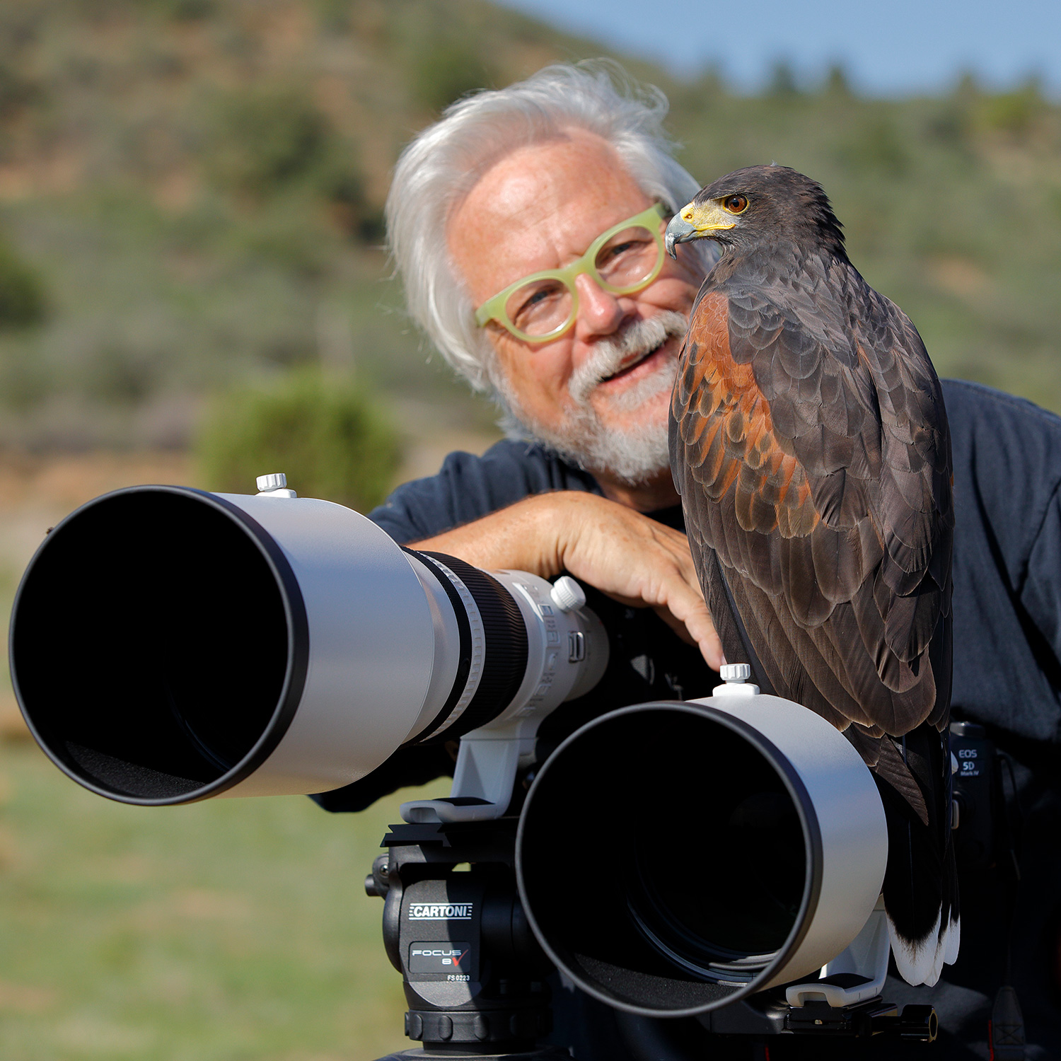 Canon Explorers of Light Series Q&A with photographer Bruce Dorn – Portrait of Bruce Dorn with an eagle sitting on his canon lenses.