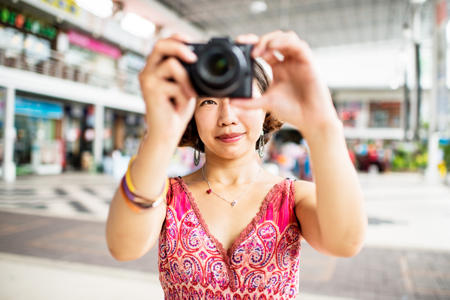 Woman at an out door shopping mall taking a photograph.