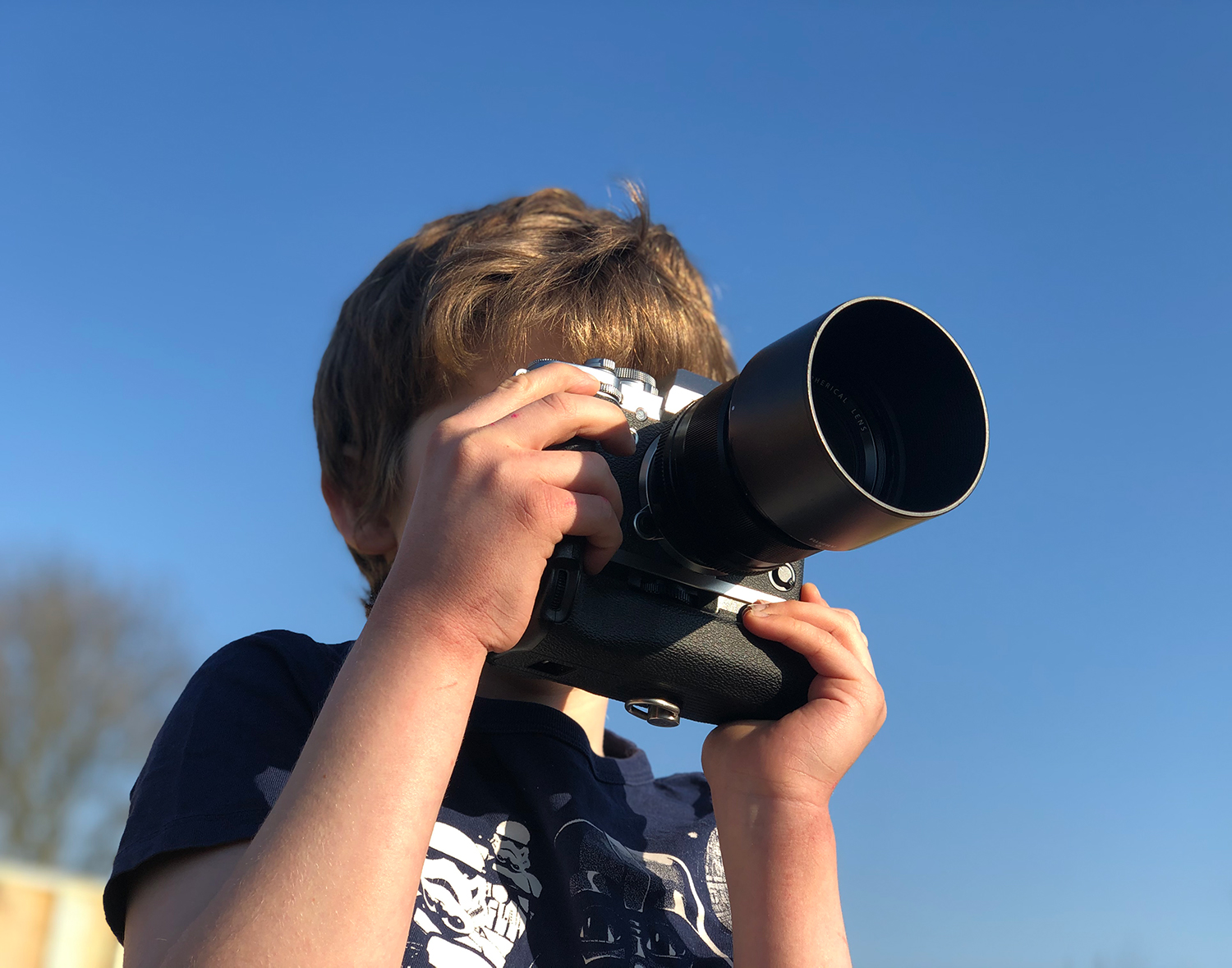 A small boy photographing with the camera up to his eye. Using photography to teach your children can cover a multitude of subjects.