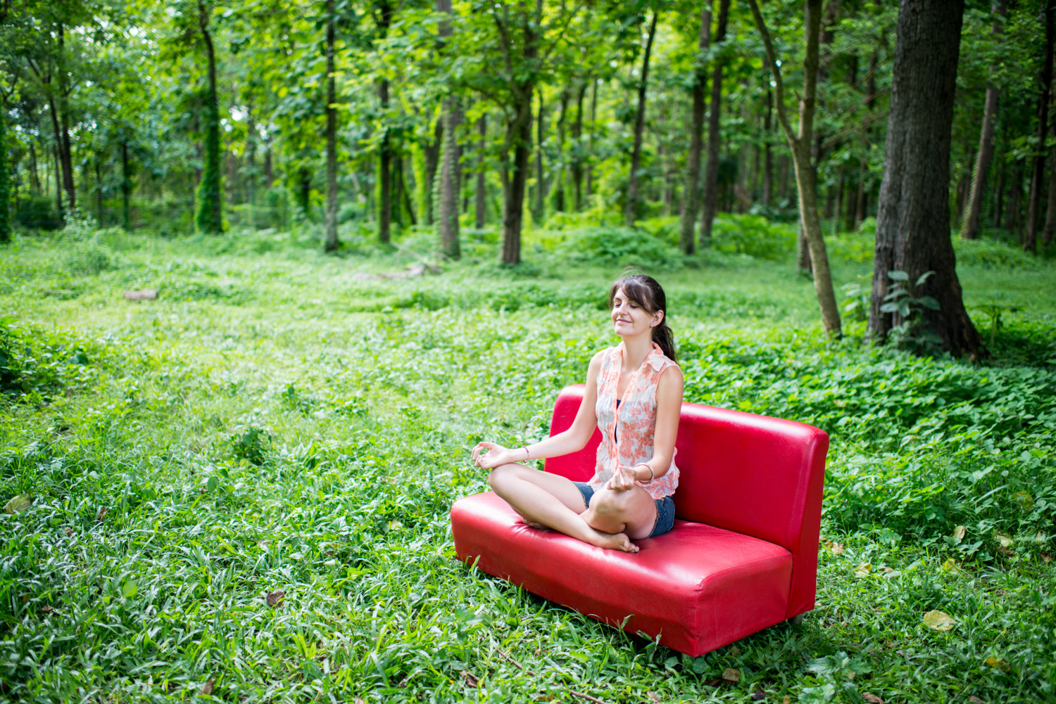 Woman on a red couch outdoors for photographing with intent