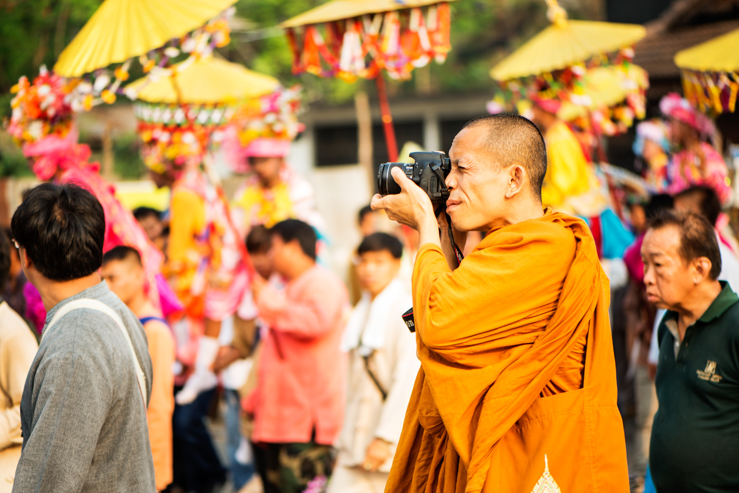 Monk photographing with intent outdoors at a parade