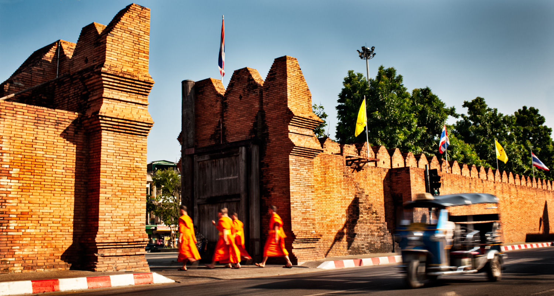 Monks walking through a gate in Thailand