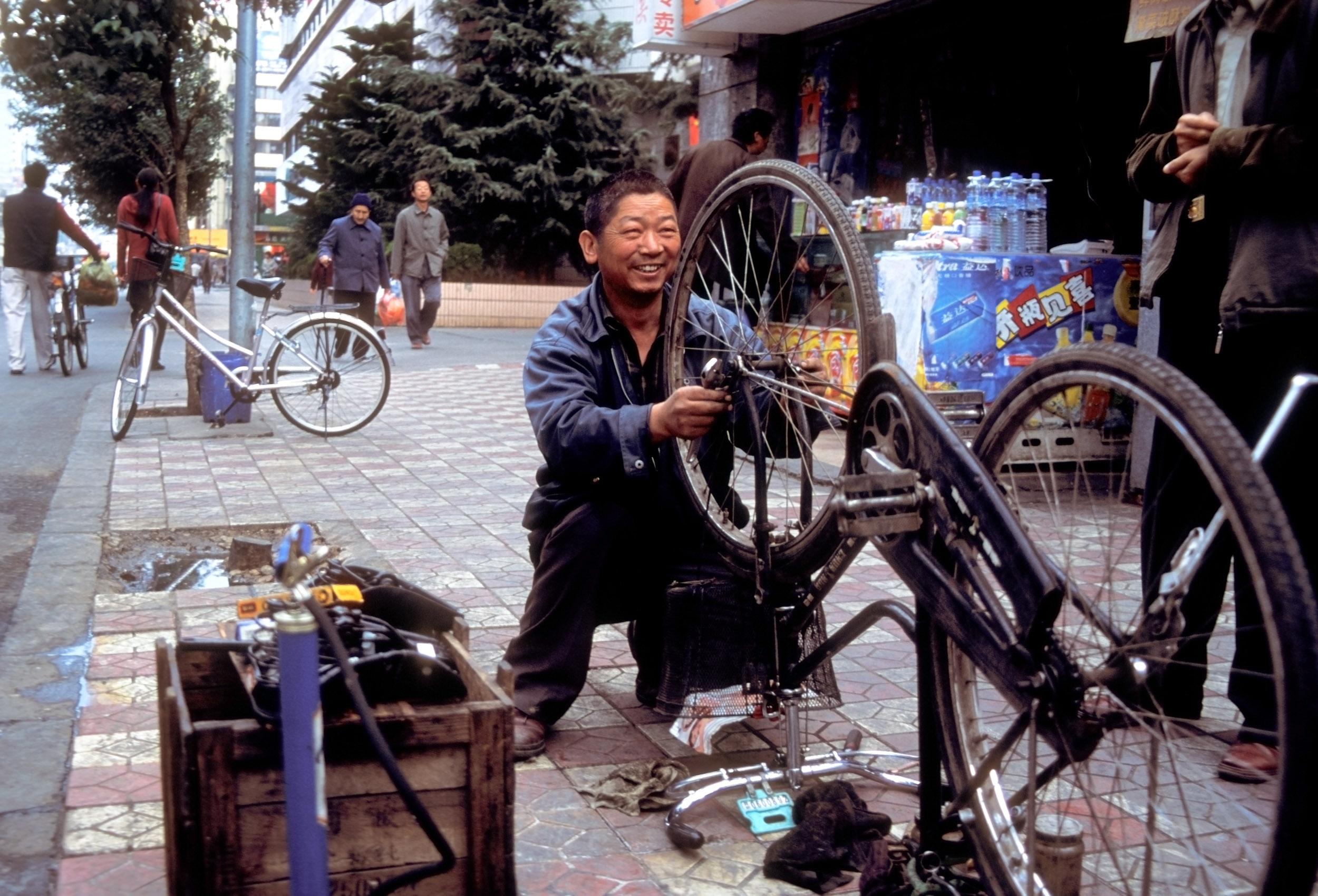 © Kevin Landwer-Johan. Conserto de bicicletas na rua na China