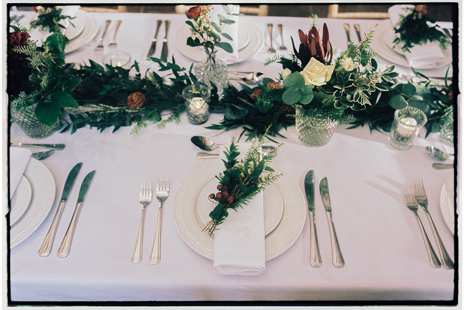 A table setting for a wedding on white linen