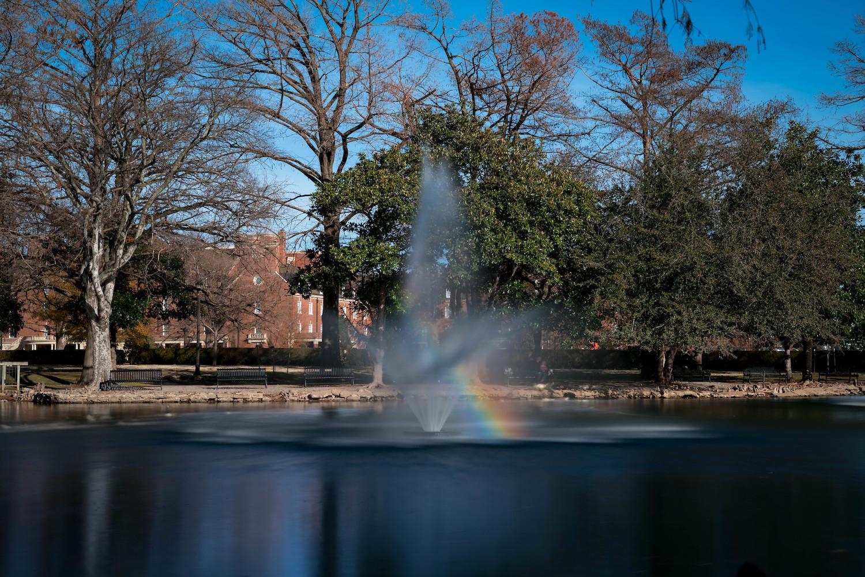fountain in a park with a rainbow