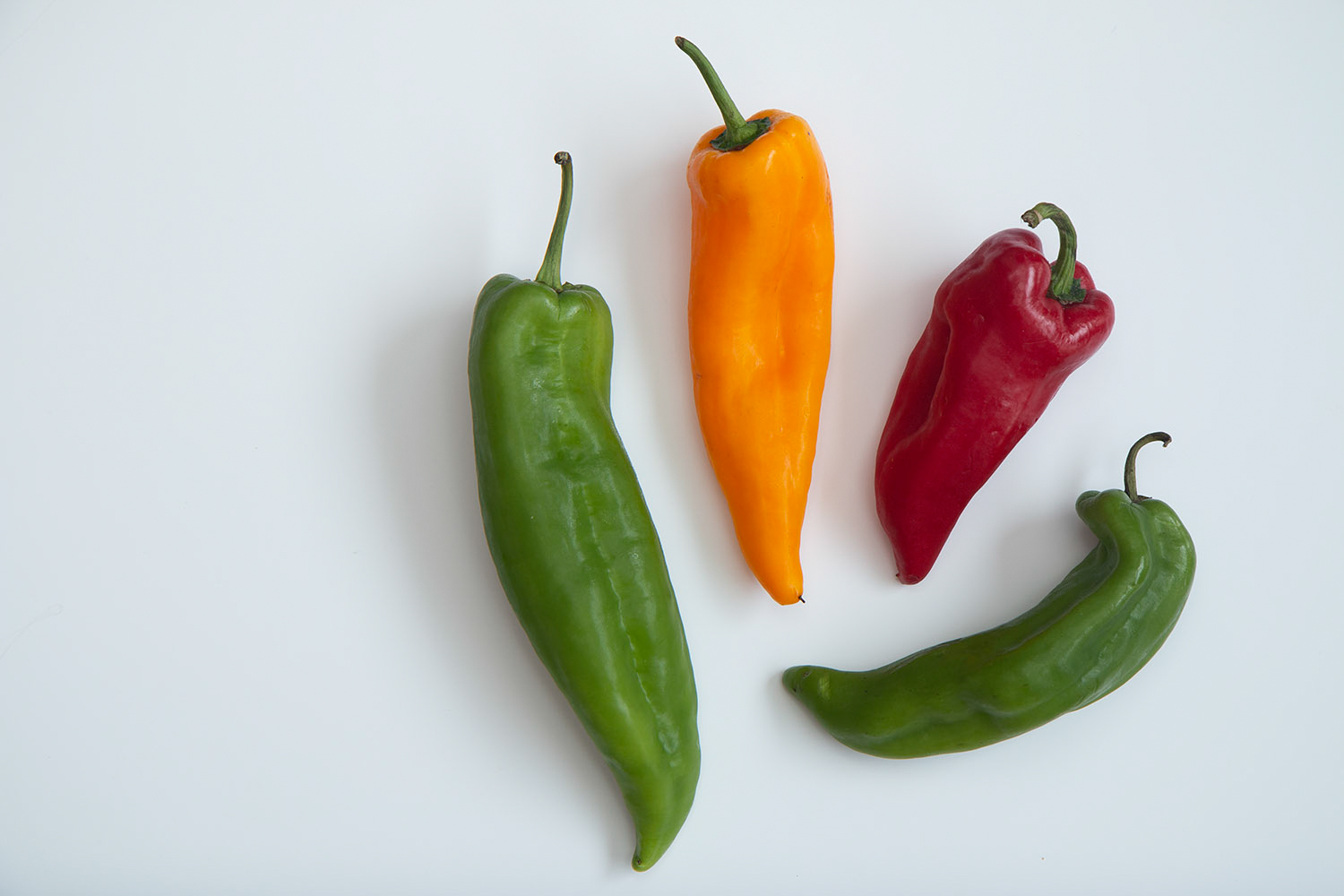 selection of chili peppers on white