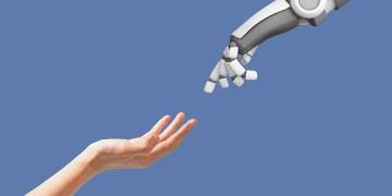 keuntungan kerugian ai keuntungan dan kerugian artificial intelligence - human hand and robot hand with empty space on blue FSWGCZT - Keuntungan dan Kerugian Artificial Intelligence