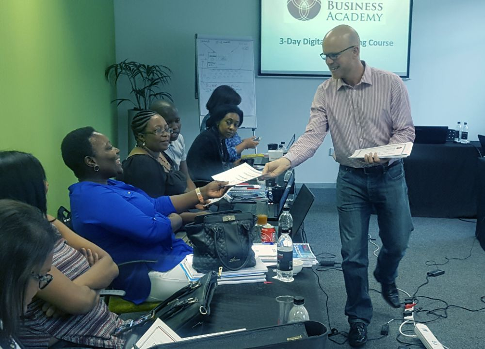 hugh mccabe handing certificates to students during digital marketing course