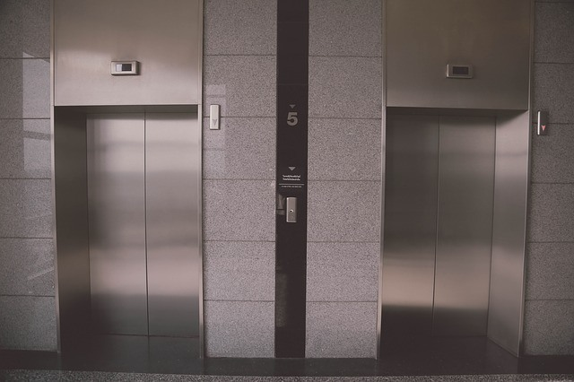 Two silver elevators in a lobby