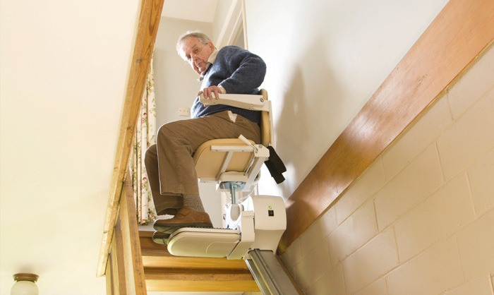 Old man coming down the stairs in a residential elevator lift