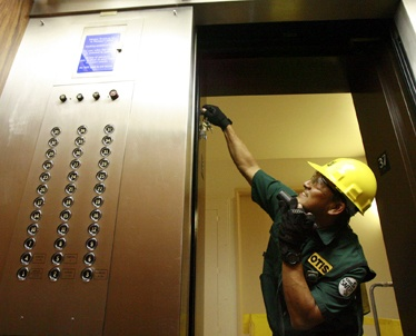 Elevator repairman with green shirt and yellow hard hat fixing and elevator door