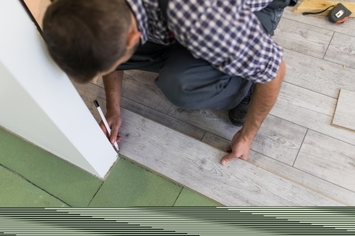 Man measuring an area against a wall to install floor panels