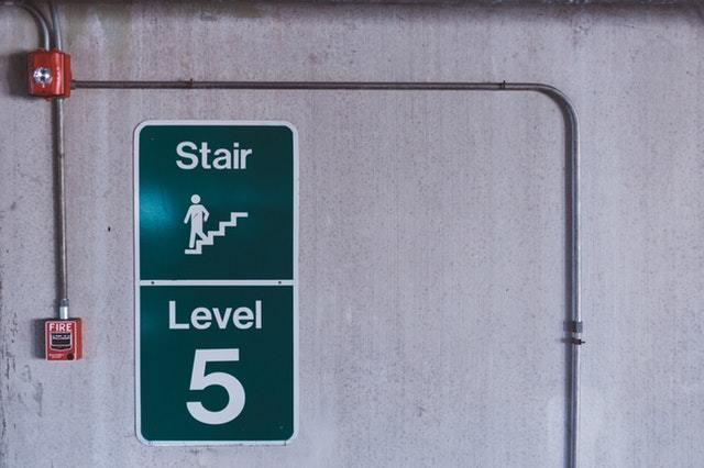 A green sign signaling stair access and floor 5. There is a red fire alarm on the wall. Insuring that fire alarms are functional is a key responsibility of fire protection contractors