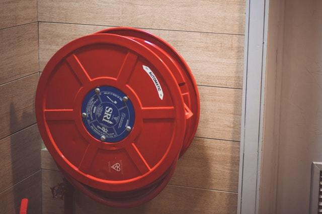 Red fire hose holder attached to the wall
