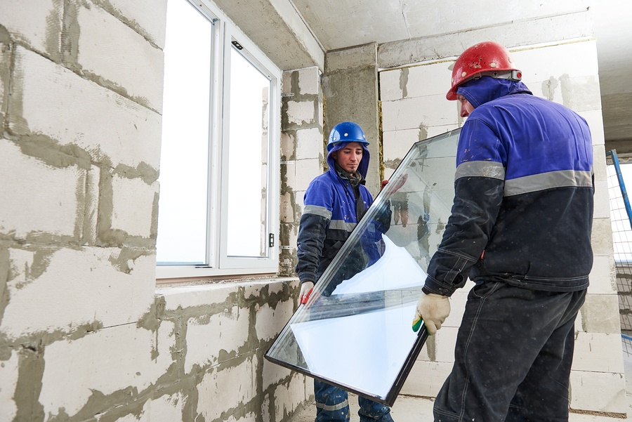 Two glazing contractors installing a window