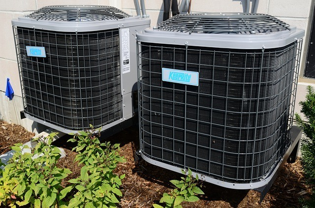 Two large commercial AC units outside of a home