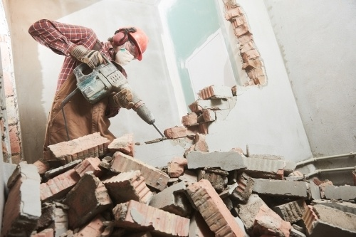 Man demolishing a wall with protective gear and a helmat