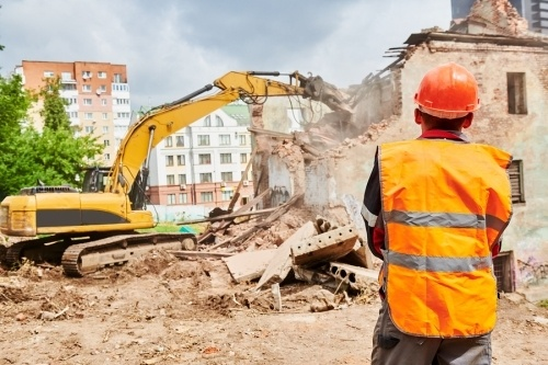 Demolition contractor overseeing a bulldozer destroy a brick building