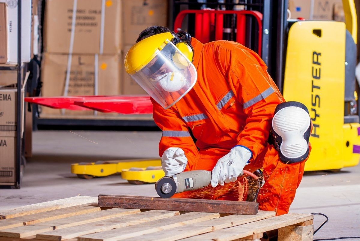 A construction worker wearing an orange body suit and protective mask finishing a piece of wood in a shop