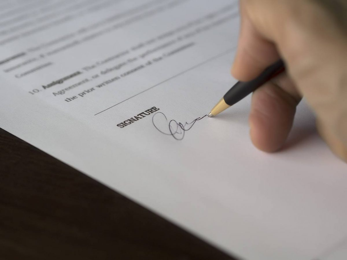 A hand filling out a contract. The contractor license law portion is 50% of the exam