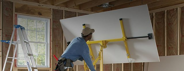 a drywall contractor installing a large piece of gysum board.