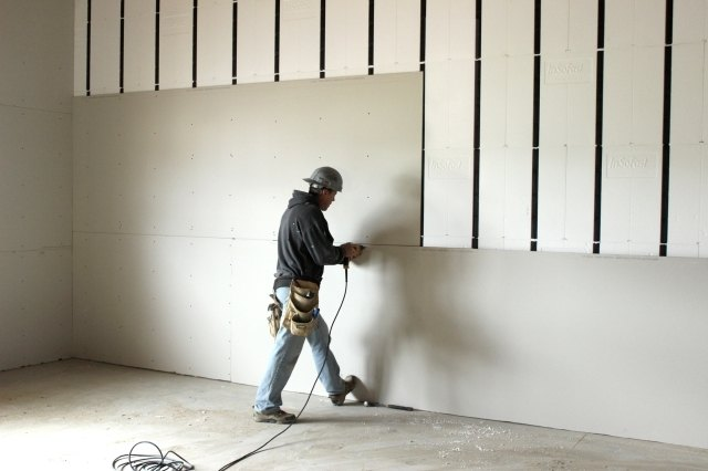 Man installing gypsum board on a construction site un-supervised