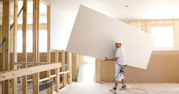 Man carrying a large rectangular piece of gypsum board beginning the drywall process