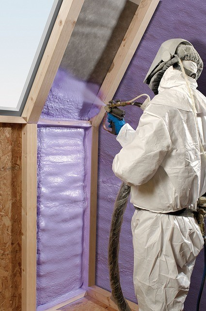 an insulation contractor spraying purple foam between two wooden boards in an attic