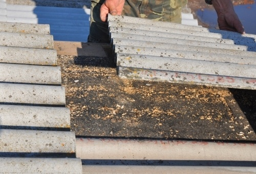 a man removing an asbestos roof panel by hand. The Contractors State license board may ask to see documentation of your experience before you are allowed to take the C-22 license exam