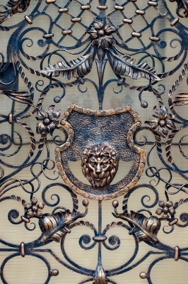 a highly detailed metal gate with bending metal features and a lions head