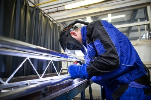 A metal contractor wearing a protective mask, welding a large metal piece in a shop