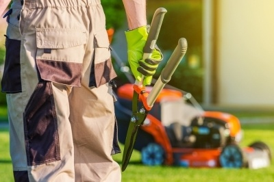 Man holding shears with a lawnmower in the background