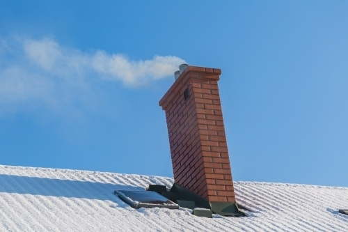 a brick chimney on top of a roof in the day time